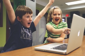A photo of children excited about using the computer